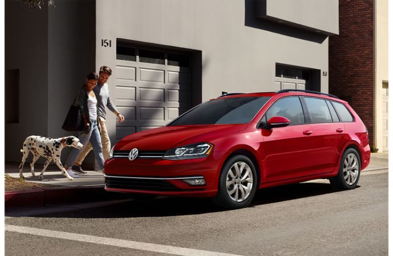 2019 Volkswagen Golf SportWagen exterior shot with tornado red paint color parked on a street as a couple and their dog walk by