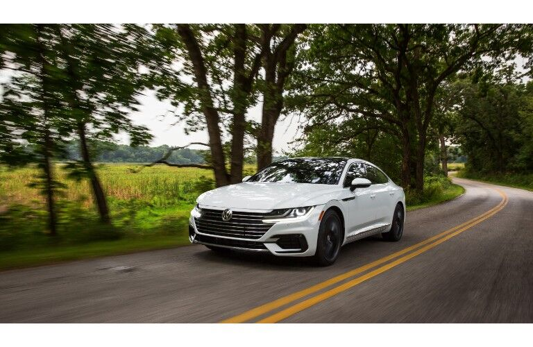 2019 Volkswagen Arteon R-Line exterior shot with white paint color driving in the country through a forest road