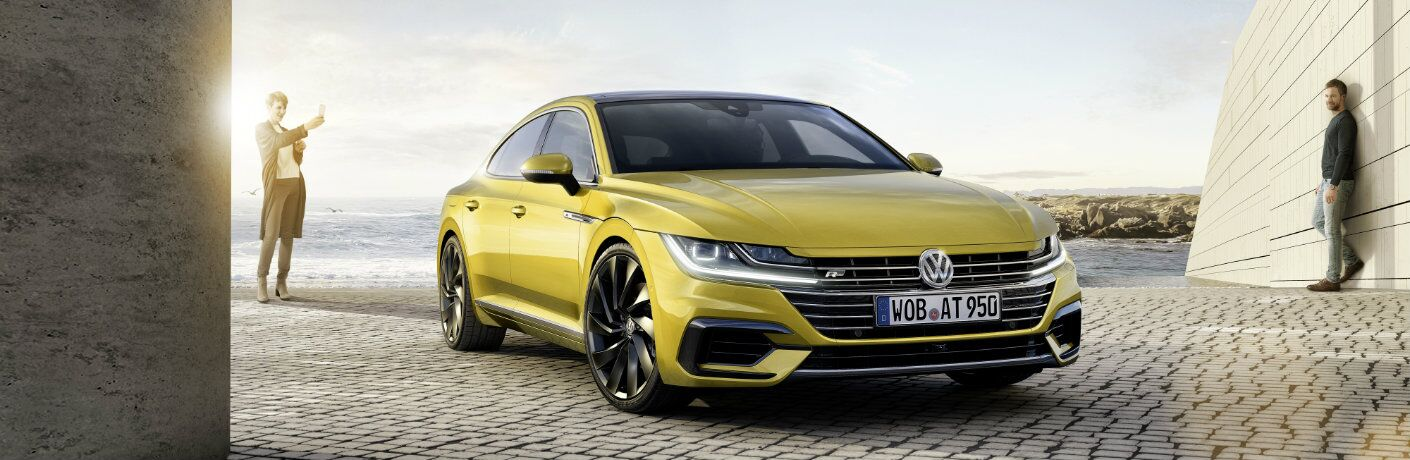 2019 Volkswagen Arteon exterior shot yellow paint job parked tiles next to the sea as two men look at it in admiration