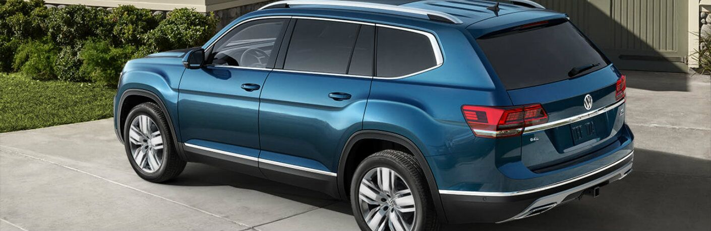 2019 Volkswagen Atlas SEL exterior rear shot with tourmaline blue paint color parked on a driveway outside a garage