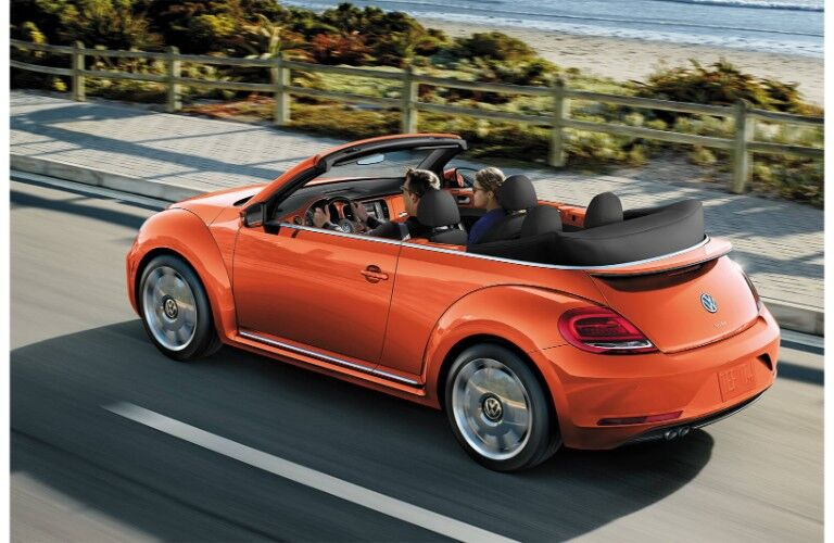 2019 Volkswagen Beetle Convertible exterior overhead shot of orange paint color driving near the sea