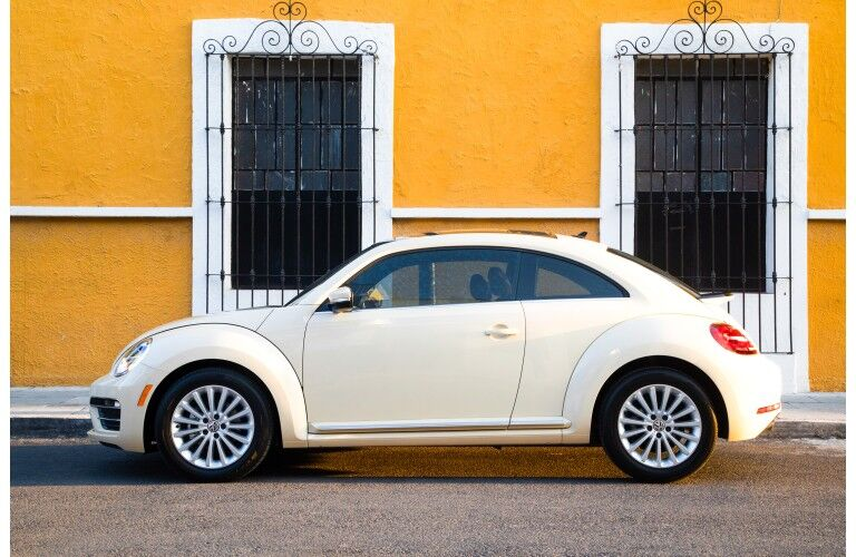2019 Volkswagen Beetle Final Edition exterior side shot with white yellow beige paint color parked outside a yellow painted building