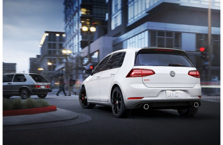 2019 Volkswagen Golf GTI exterior rear shot with white color paint job driving around a turning circle round about in the middle of city