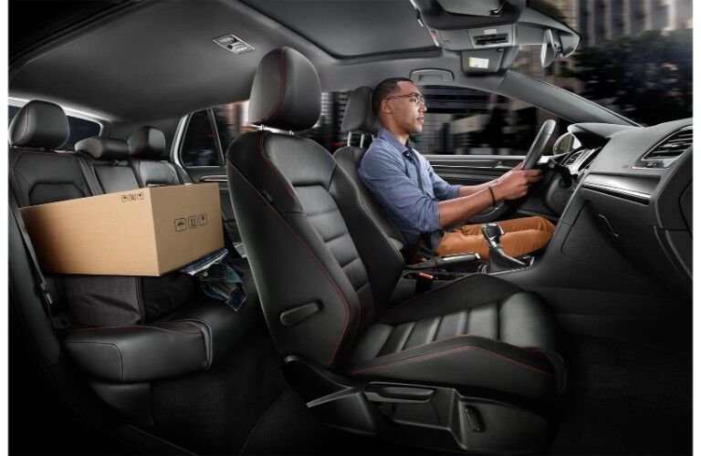 2019 Volkswagen Golf GTI interior side shot of seating rows and upholstery material as a man drives through the city with packages in the back