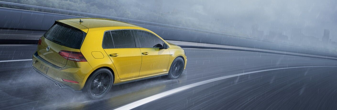 2019 Volkswagen Golf R exterior shot with ginster yellow paint color driving through the rain on a cloudy highway
