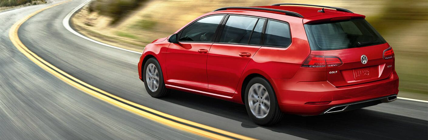 2019 Volkswagen Golf SportWagen exterior read shot with red paint color driving around a curve on a mountain road