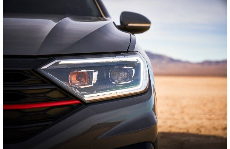 2019 Volkswagen Jetta GLI exterior shot closeup of headlight design, grille, and GLI red strip with a desert background