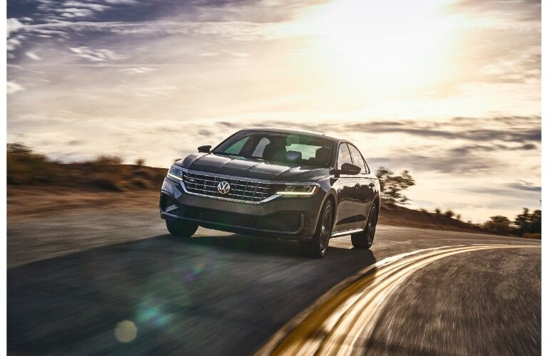 2020 Volkswagen Passat exterior front shot driving over a hill as the sun shine bright in the sky behind it