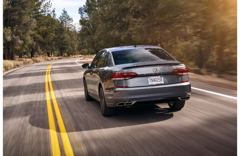 2020 Volkswagen Passat exterior rear shot of back bumper, taillights, and trunk driving between the tall trees of a forest