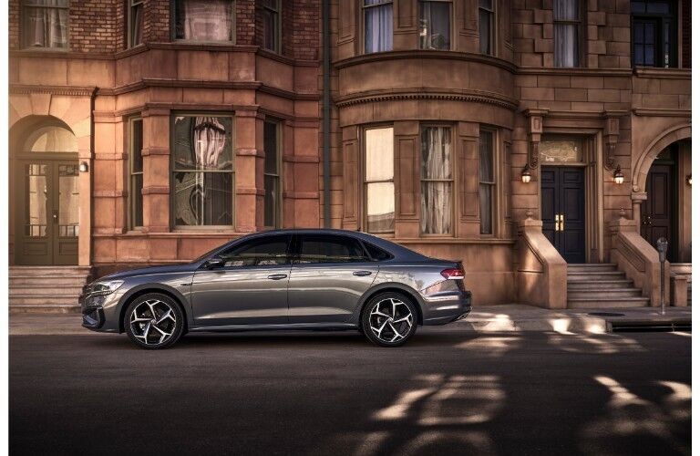 2020 Volkswagen Passat exterior side shot with gray metallic paint color parked outside a set of old stone apartment buildings
