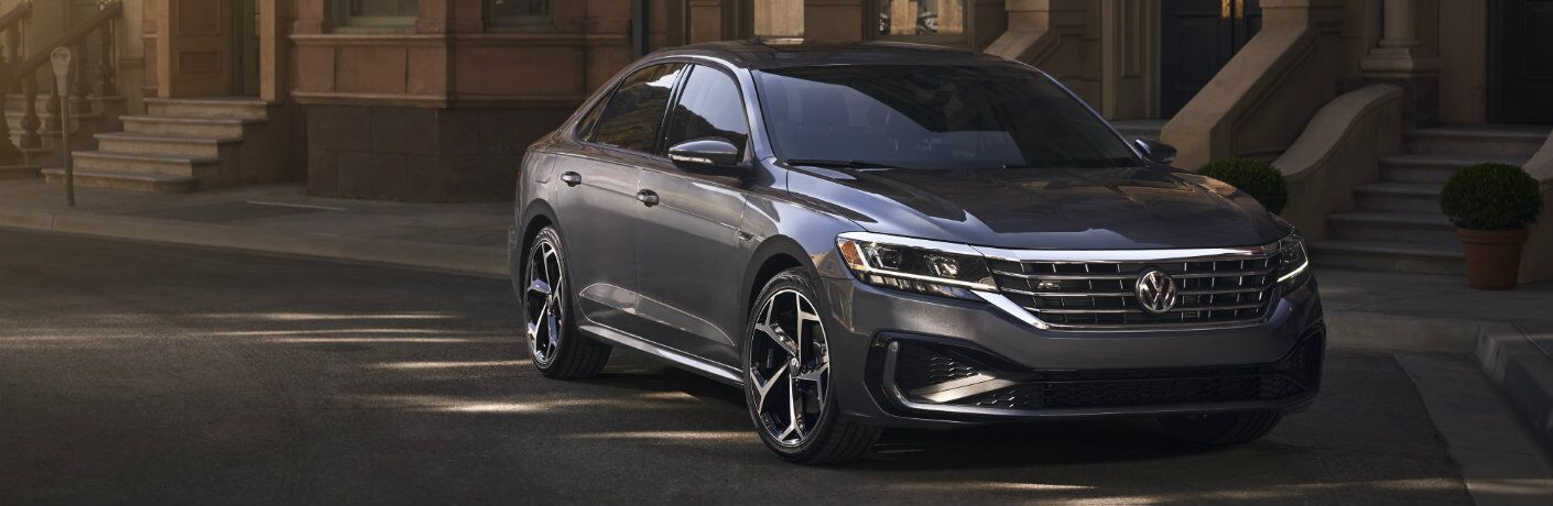 2020 Volkswagen Passat redesign exterior front shot of headlights and grille with gray paint color parked outside the stairs of a stone building