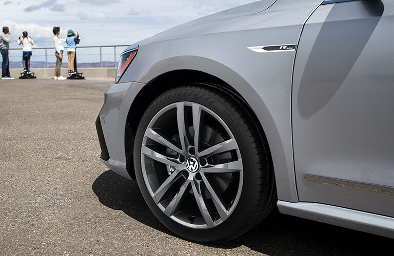 Close-up on the front left wheel of a 2019 Volkswagen Passat with a family nearby