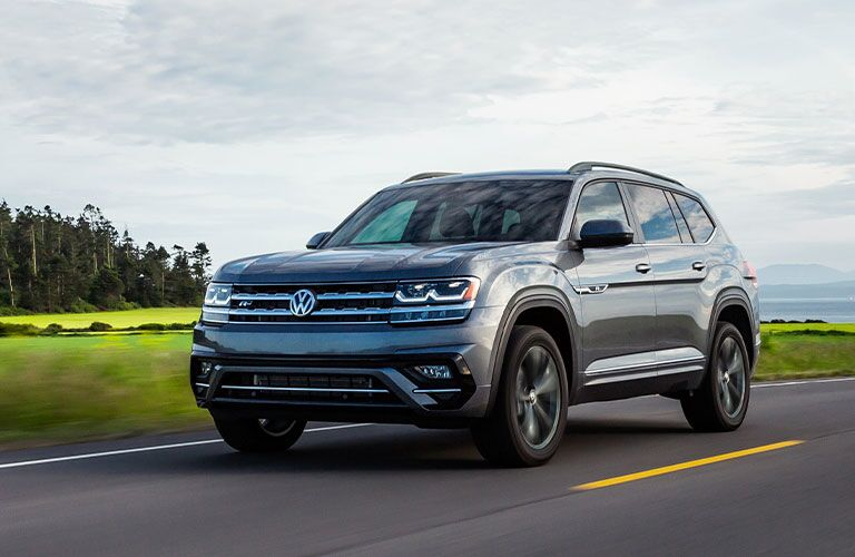 The front and side view of a gray 2020 Volkswagen Atlas driving down an open road.