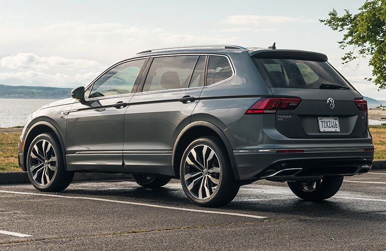 A rear and side view of a 2020 Volkswagen Tiguan parked near a lake.