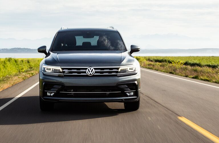 The front view of a gray 2020 Volkswagen Tiguan driving down a road