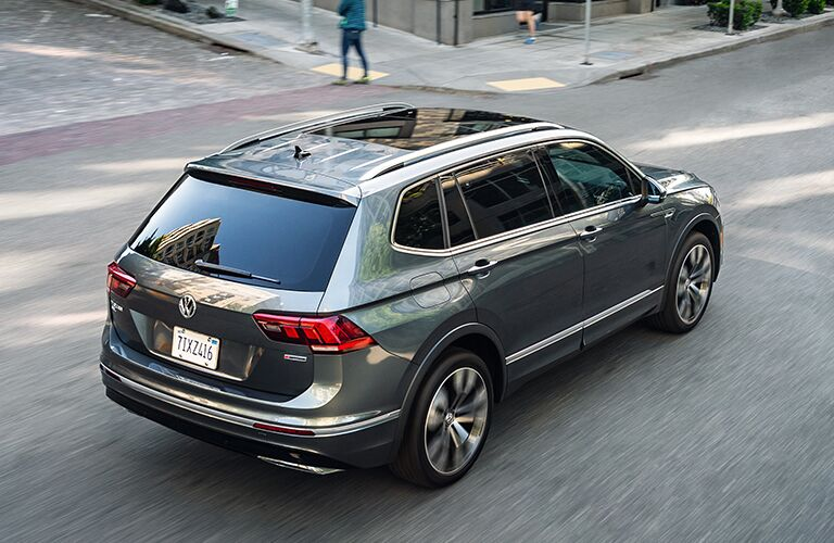 The top, rear, and side view of a gray 2020 Volkswagen Tiguan driving down the road.
