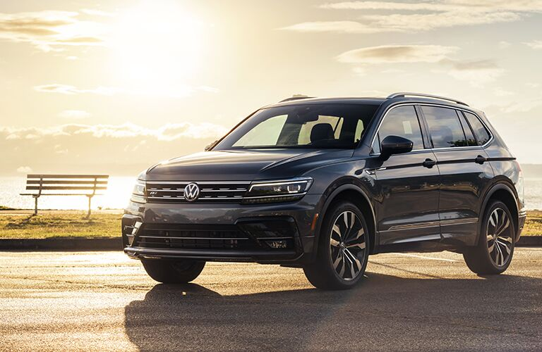 A front and side view of a gray 2020 Volkswagen Tiguan parked near a lake.