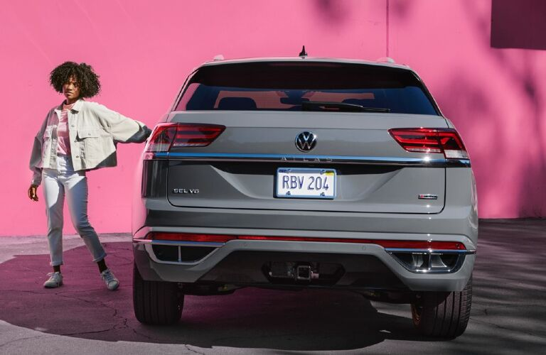 The rear side of a gray 2020 Volkswagen Atlas Cross Sport in front of a pink wall.