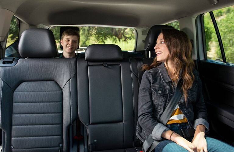 Two young kids sitting and smiling in the second and third row of a 2021 Volkswagen Atlas.