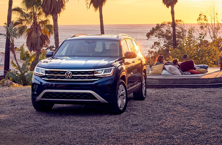 The front exterior of a blue 2021 Volkswagen Atlas at sunset.