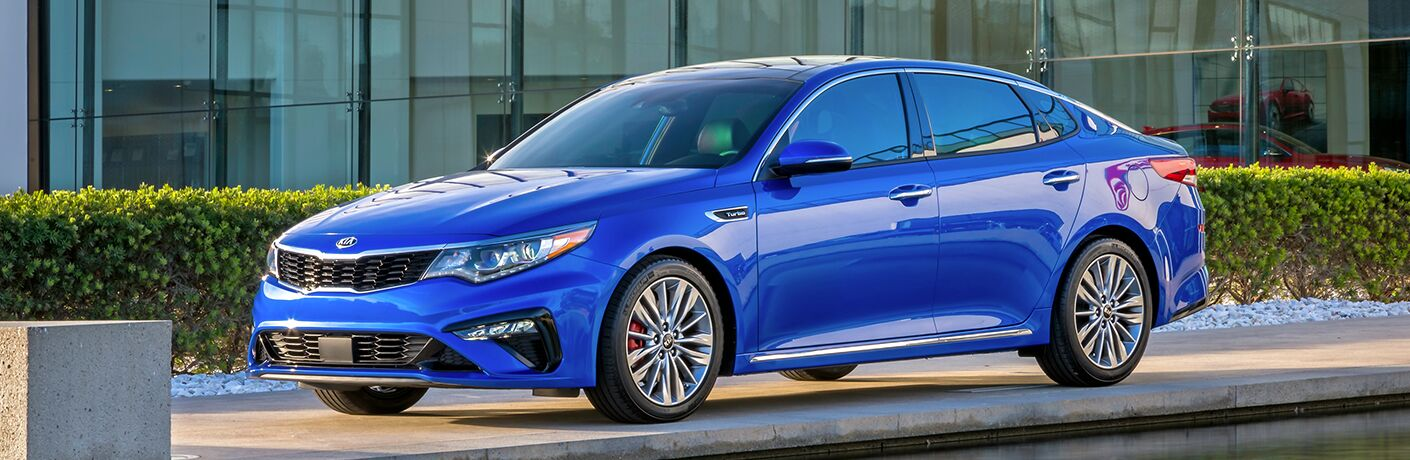 2019 Kia Optima exterior shot blue parked in front of a glass Kia dealership next to a row of bushes
