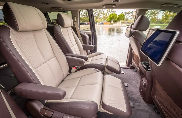 2019 Kia Sedona interior side shot of back seating upholstery, entertainment screens, and doors open into a view of lake scenery