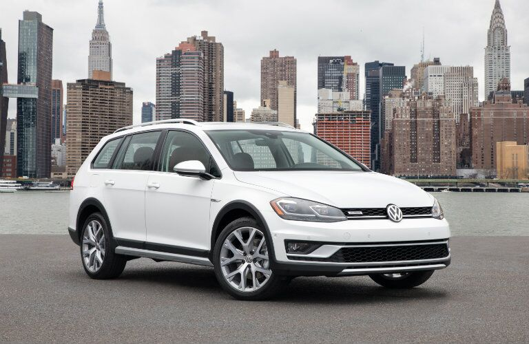 2018 Volkswagen Golf Alltrack exterior shot white paint front end angle on beach with a cityscape background