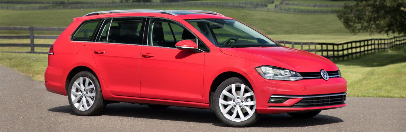 2018 Volkswagen Golf SportWagen red parked in country road by fence