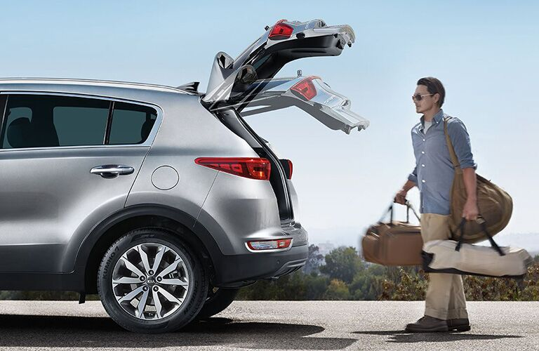 Man with hands full of luggage using the remote tailgate of the 2018 Kia Sportage