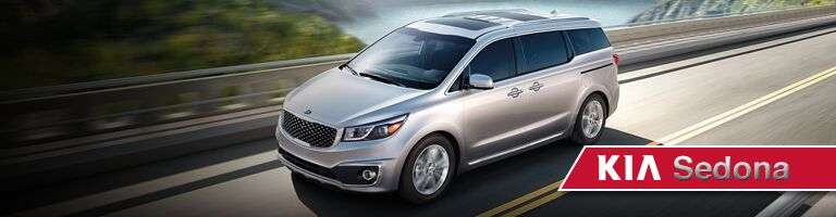Front exterior view of a gray Kia Sedona