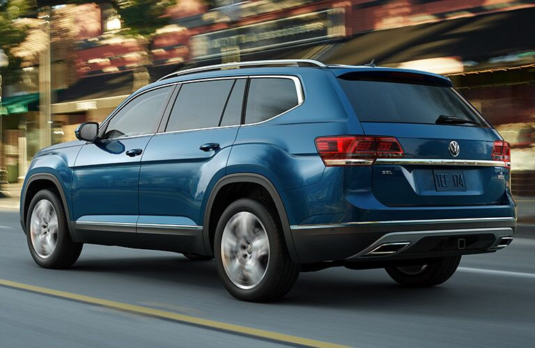 Exterior view of the rear of a blue 2019 Volkswagen Atlas driving down a city street