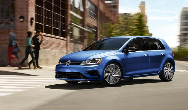 2018 Volkswagen Golf R driving outside real fast in the city past some people