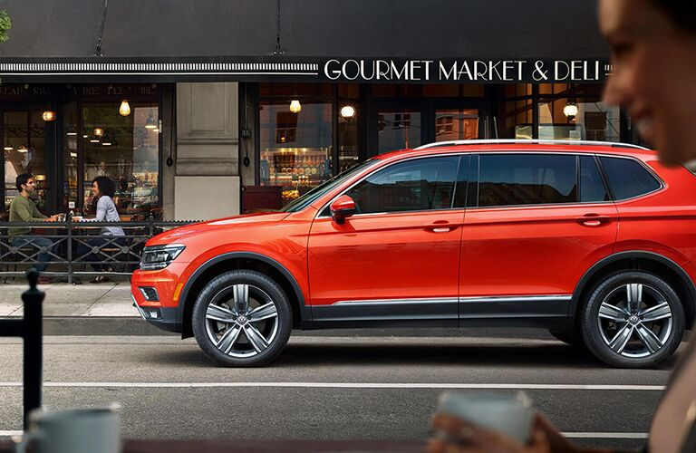 Driver view of an orange 2019 Volkswagen Tiguan parked on the side of a street in front of a deli