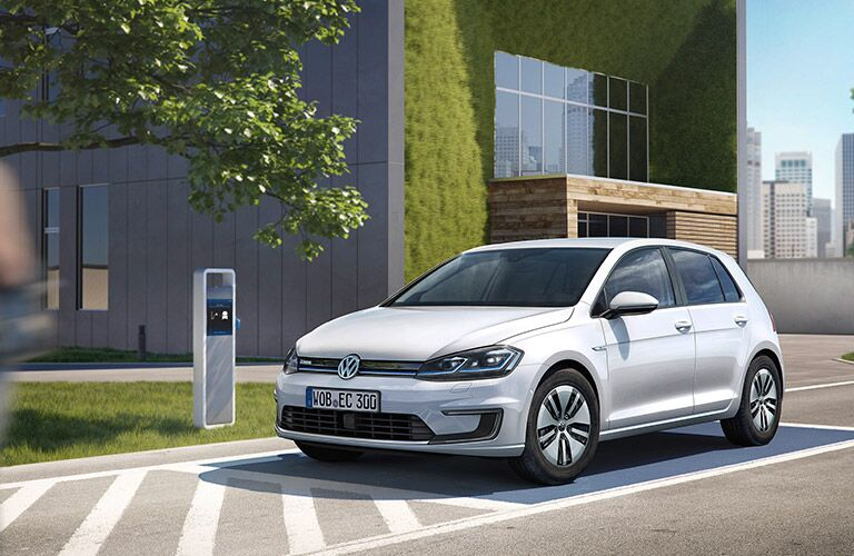 white volkswagen e-golf parked by charging station