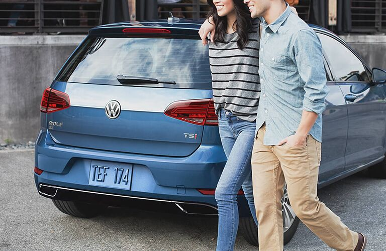 Two people walking by a blue 2019 Volkswagen Golf