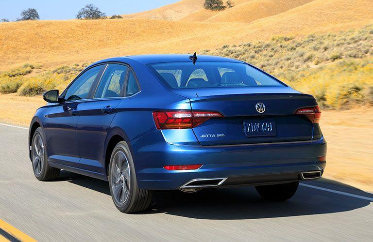 Rear view of blue 2019 Volkswagen Jetta driving through desert
