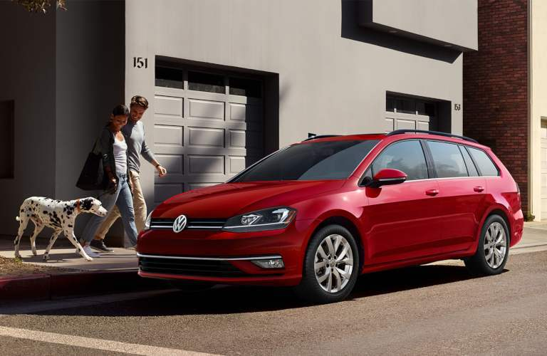 A family and their dog walking towards a parked 2019 Volkswagen Golf SportWagen