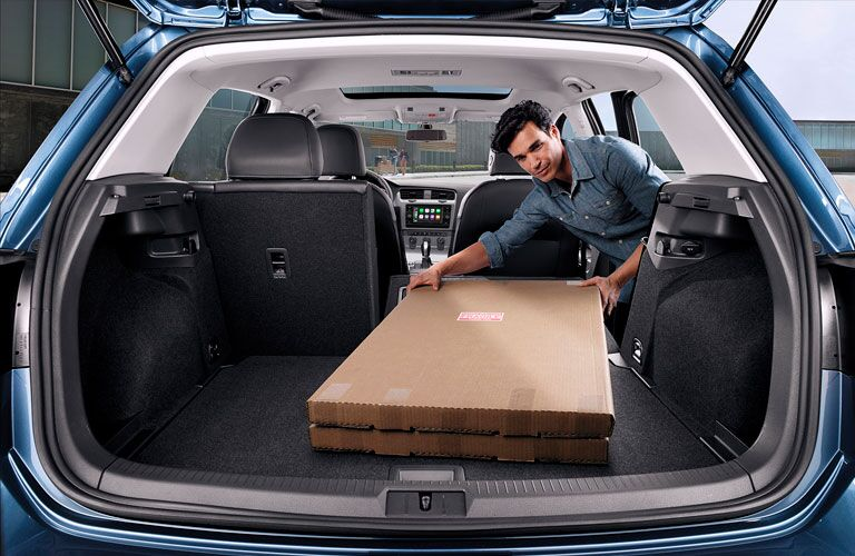 2020 Volkswagen Golf blue trunk open with man loading long box in back