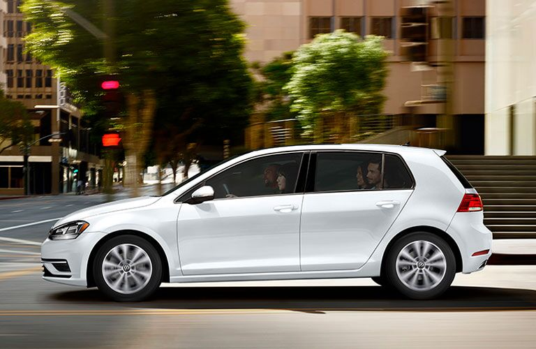 2020 Volkswagen Golf white driving through city view of driver side profile