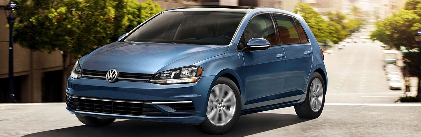 2020 Volkswagen Golf blue driving down hilly road in city turning slightly