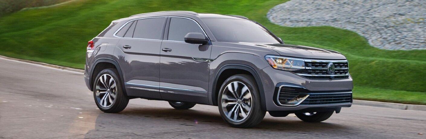 2020 Volkswagen Atlas Cross Sport Gray driving past green grass on downhill grade