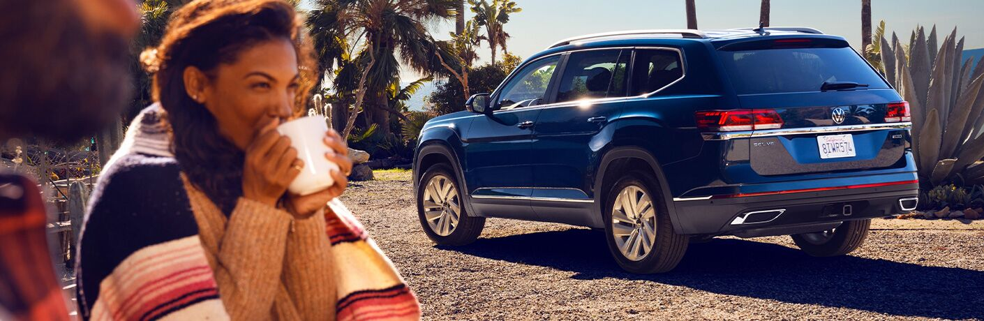 2021 Volkswagen Atlas parked by park with woman drinking from mug in foreground