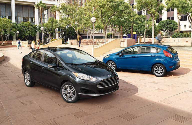 black 2018 Ford Fiesta Sedan and blue 2018 Ford Fiesta Hatchback parked in a city square