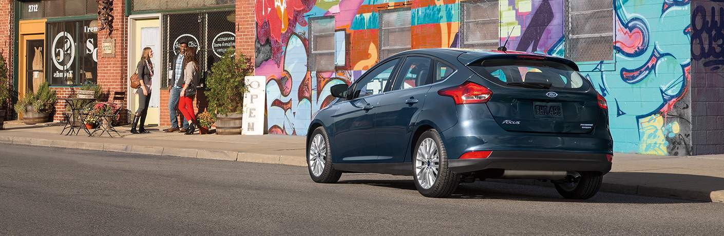 blue 2018 Ford Focus Hatchback parked in front of a building with graffiti on it