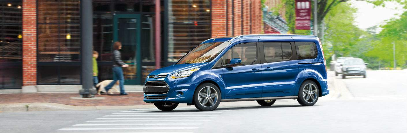 side view of a blue 2018 Ford Transit Connect Passenger Wagon turning a corner