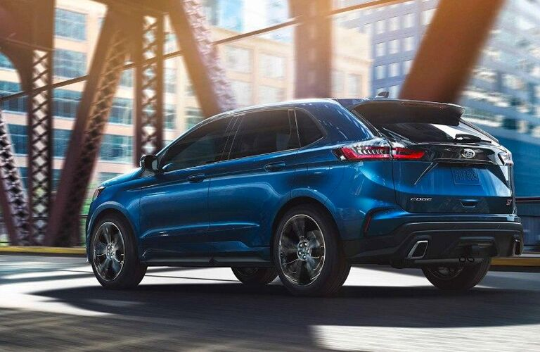 rear view of a blue 2019 Ford Edge ST driving over a bridge