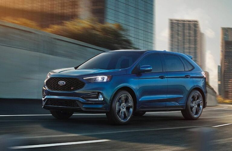 side view of a blue 2019 Ford Edge ST driving on a highway