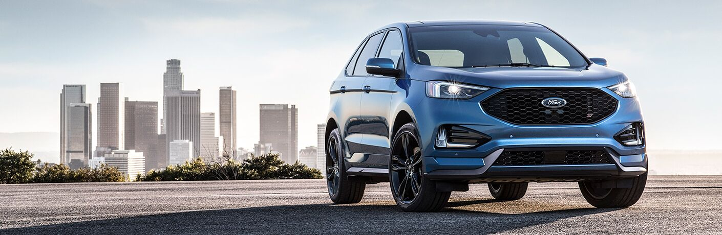 front view of a blue 2019 Ford Edge ST with a city skyline in the background