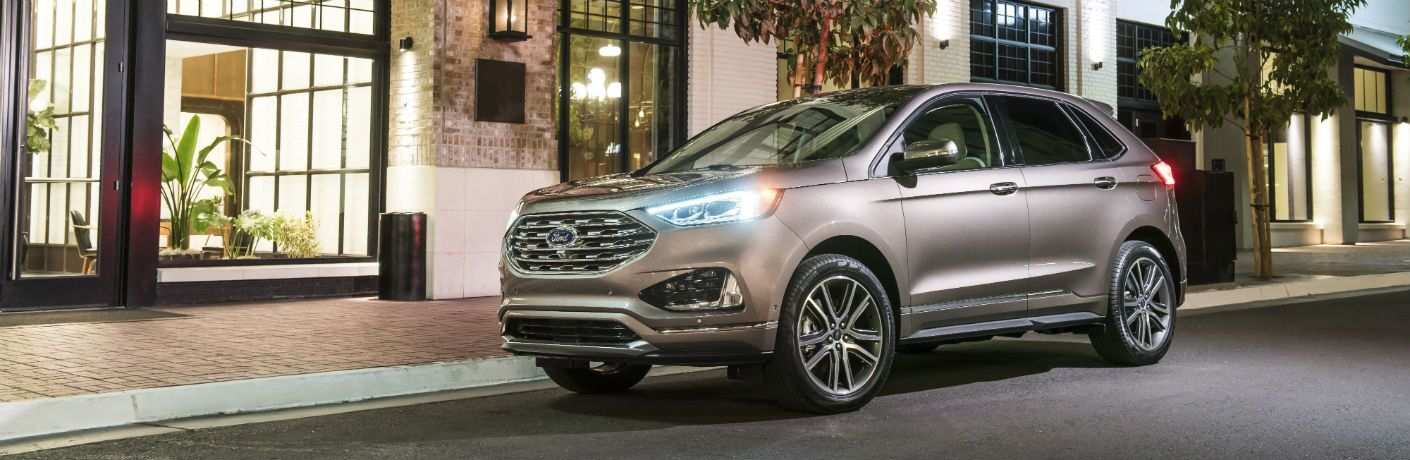 side view of a silver 2019 Ford Edge Titanium Elite parked outside a city residence