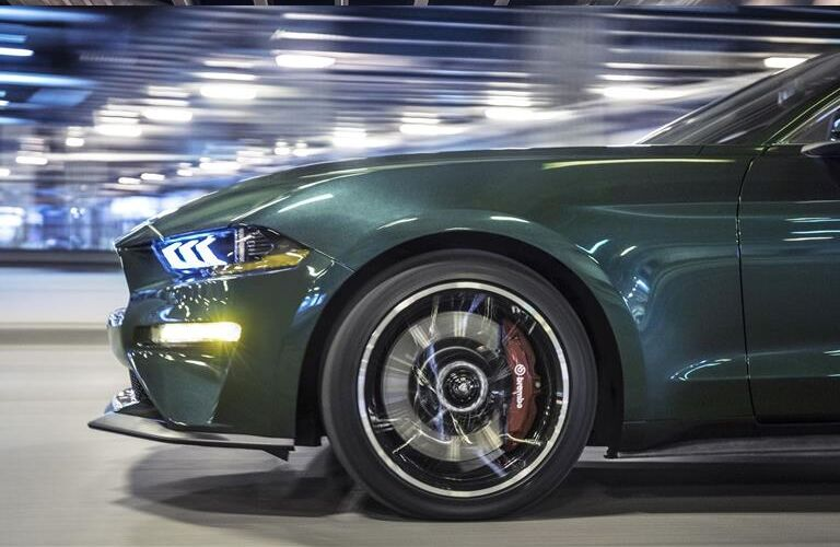 side view of the front half of a green 2019 Ford Mustang Bullitt's exterior with special emphasis on its wheel